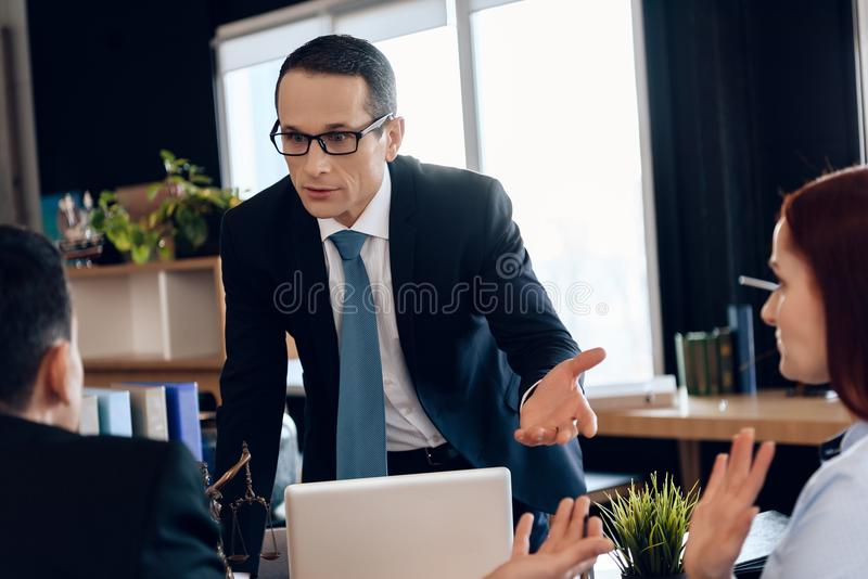 Divorce lawyer points hand at redhead woman next to man sitting in office. Back view. royalty free stock photos