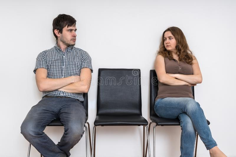 Divorce and relationship difficulties concept. Man and woman sitting on chairs and looking at each other. Divorce and relationship difficulties concept. Man and stock image