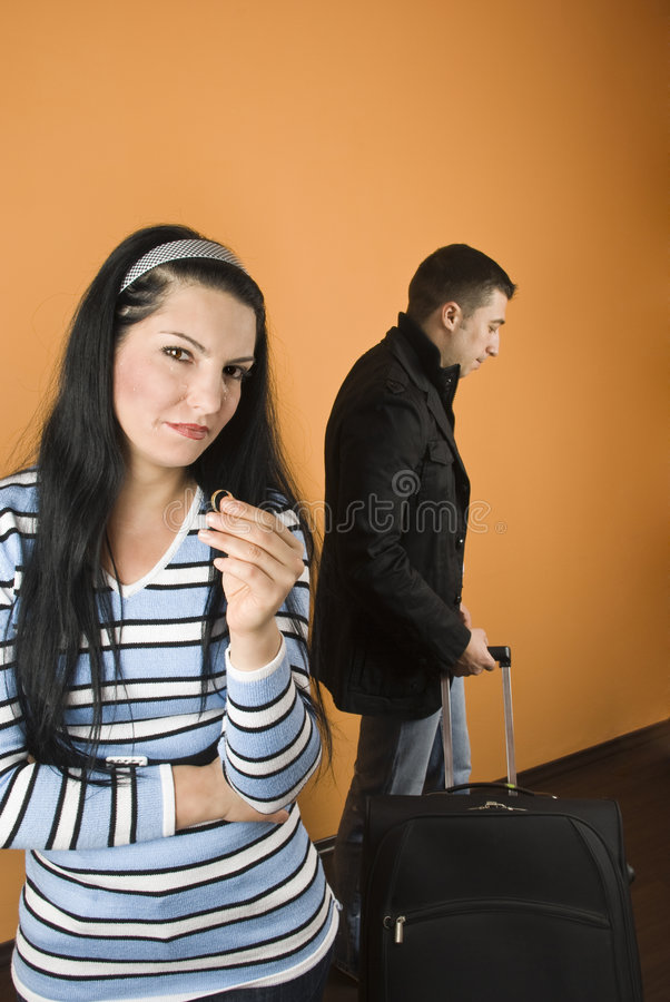 Divorced. Couple divorced,woman crying and stand with arms crossed and holding the wedding ring while the man leaves home,check also stock image