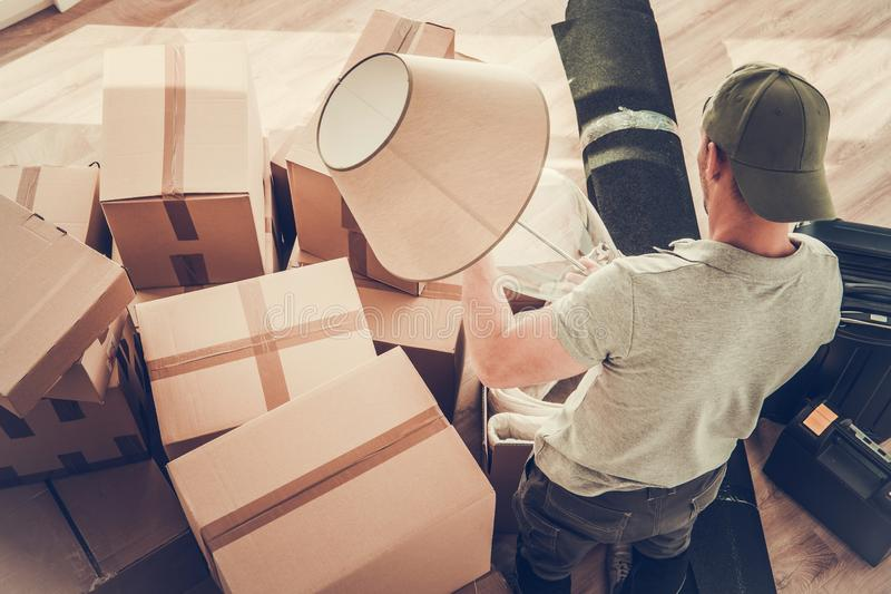 Divorced Men Moving Out. Caucasian Divorced Men in His 30s Moving Out From His Home. Staying Between Cardboard Boxes Preparing to Pack His Lamp stock photography