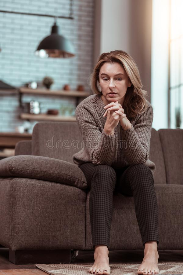 Divorced woman feeling lonely and sad sitting home alone. Lonely and sad. Divorced woman feeling lonely and sad sitting on the sofa while being home alone royalty free stock photography