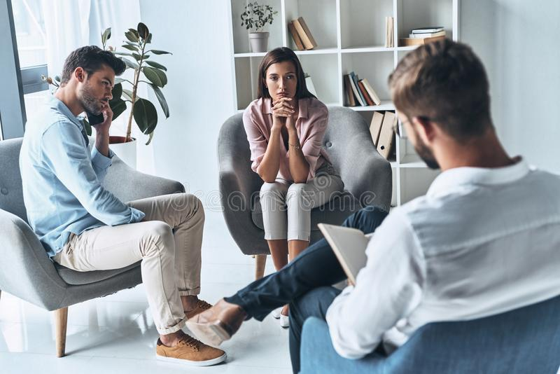 Almost divorced. Young married couple talking while sitting on the therapy session with psychologist stock photography