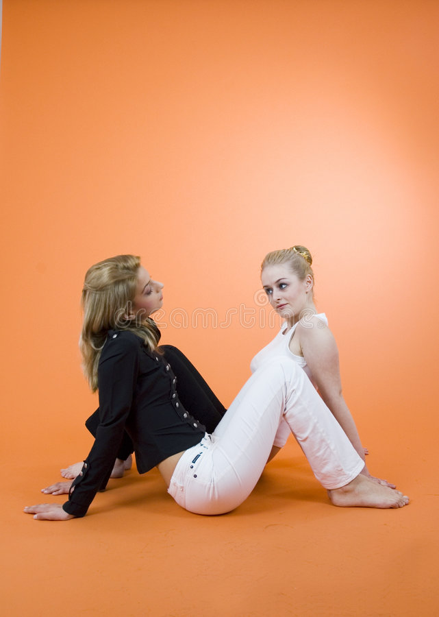 Divulging A Secret. Two young women sitting on the floor in opposite directions, having a conversation stock image