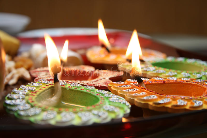Diwali diyas. Close up of traditional diwali (Indian festival) decorated diyas with sweets, fruits in background