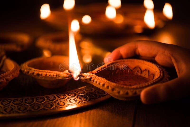 Diwali felice - passi la tenuta o l'illuminazione o l'organizzazione il diya di diwali o della lampada dell'argilla fotografia stock libera da diritti