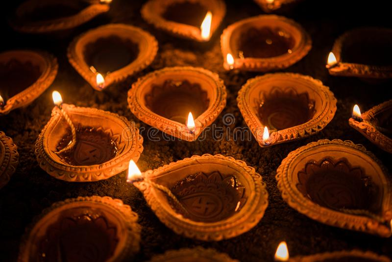 Diwali feliz - lámparas del diya o de aceite de la terracota sobre la superficie o la tierra, foco selectivo de la arcilla imagen de archivo libre de regalías