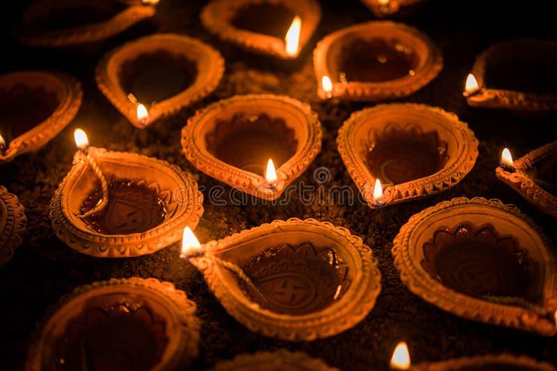 Diwali feliz - lâmpadas do diya ou de óleo da terracota sobre a superfície da argila ou a terra, foco seletivo imagem de stock royalty free