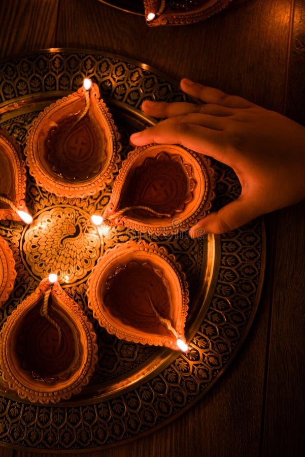 Diwali heureux - remettez se tenir ou éclairage ou s'charger du diya de diwali ou de la lampe d'argile dans le plat en laiton, fo images stock