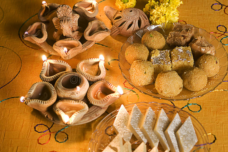Diwali Lamps with Indian sweets (mithai). A table setting of Diwali Lamps with different Indian sweets on the table