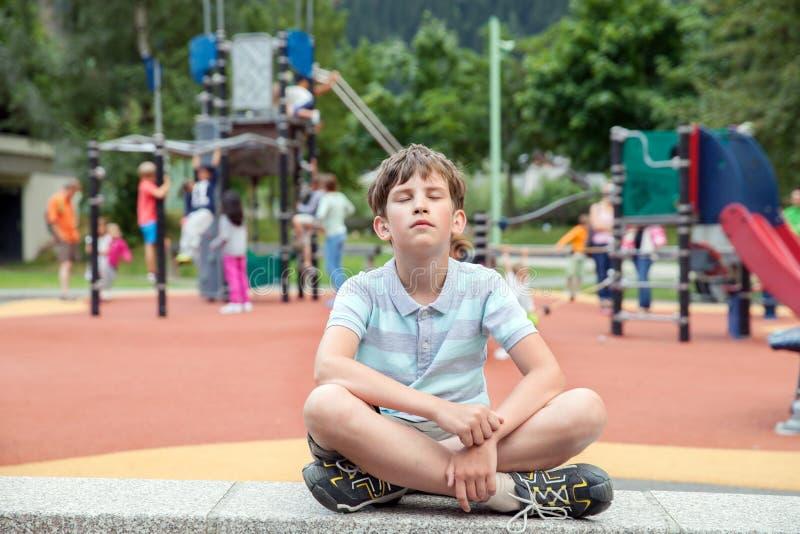 Dix ans de garçon se reposent sur le terrain de jeu des cheldren photos libres de droits