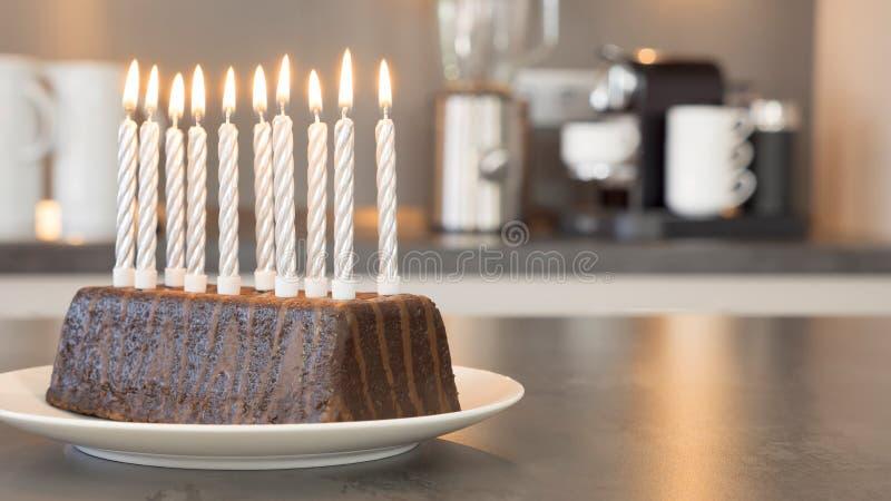 Dix bougies brûlantes sur un gâteau d'anniversaire dans une cuisine moderne photo stock