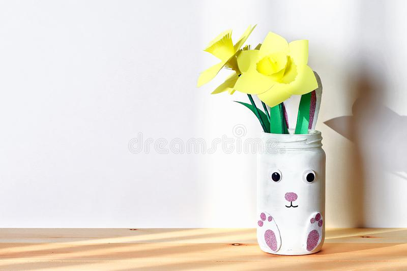 DIY复活节与水仙,从玻璃瓶子,毛毡,在白色墙壁背景的眼睛的黄水仙的花瓶兔宝宝 库存照片