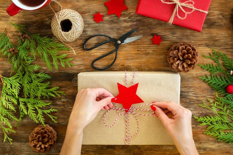 DIY礼品包装材料 包裹在土气木桌上的妇女美好的红色圣诞礼物 顶上看法圣诞节包裹 库存照片