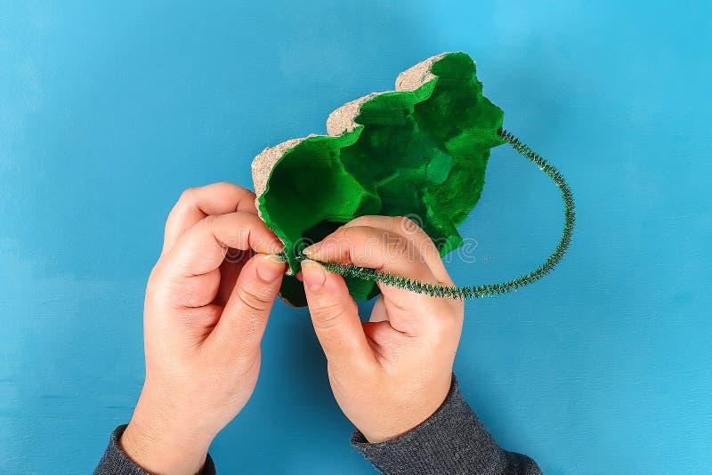 DIY篮子从纸板盘子,皱纹纸,在蓝色背景的宋绒线词根的复活节彩蛋 免版税库存图片