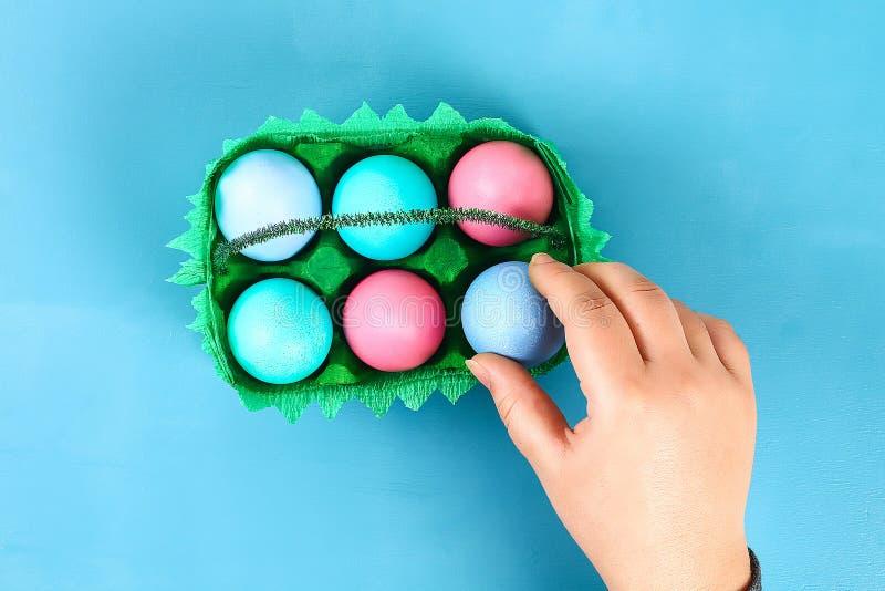 DIY篮子从纸板盘子,皱纹纸,在蓝色背景的宋绒线词根的复活节彩蛋 库存图片