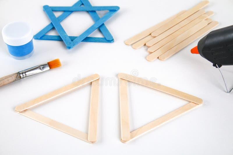 DIY Ντεκόρ Hanukkah Αστέρι του Δαυίδ από τα ραβδιά παγωτού σε έναν άσπρο ξύλινο πίνακα Οδηγός, βαθμιαία σχετικά με τη φωτογραφία  στοκ εικόνα