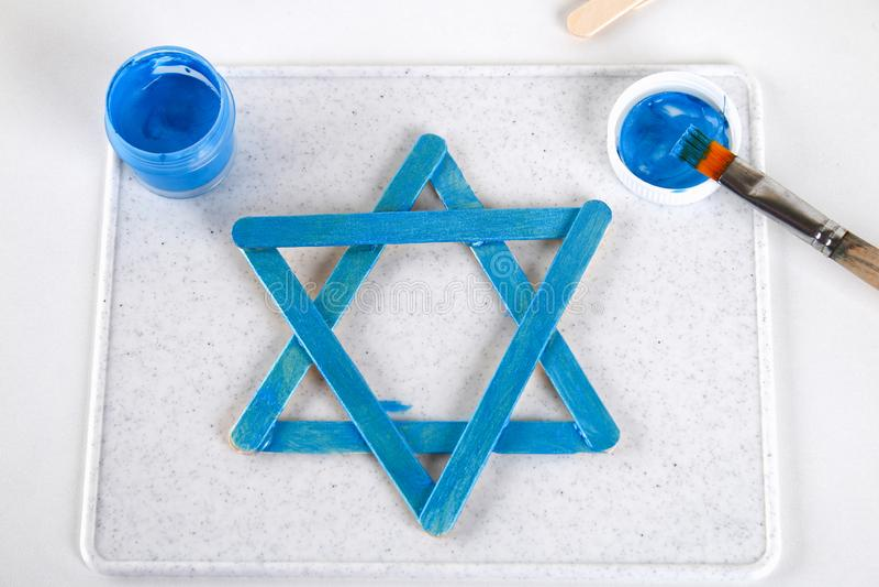 DIY Ντεκόρ Hanukkah Αστέρι του Δαυίδ από τα ραβδιά παγωτού σε έναν άσπρο ξύλινο πίνακα Οδηγός, βαθμιαία σχετικά με τη φωτογραφία  στοκ εικόνα με δικαίωμα ελεύθερης χρήσης