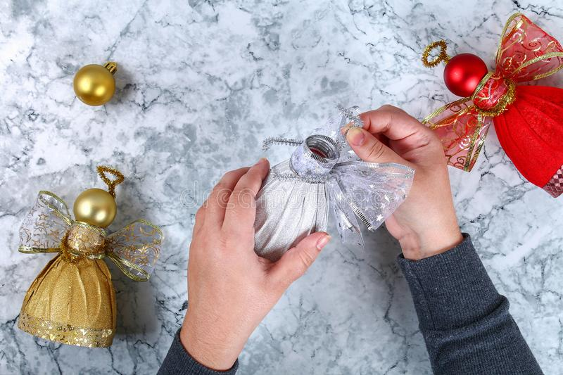 Diy Angel plastic bottle. Guide on the photo how to make a decorative angel from a bottle, self-adhesive shiny paper, ribbon and a royalty free stock photo