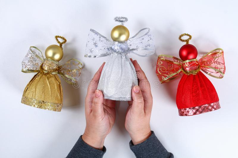 Diy Angel plastic bottle. Guide on the photo how to make a decorative angel from a bottle, self-adhesive shiny paper, ribbon and a stock image