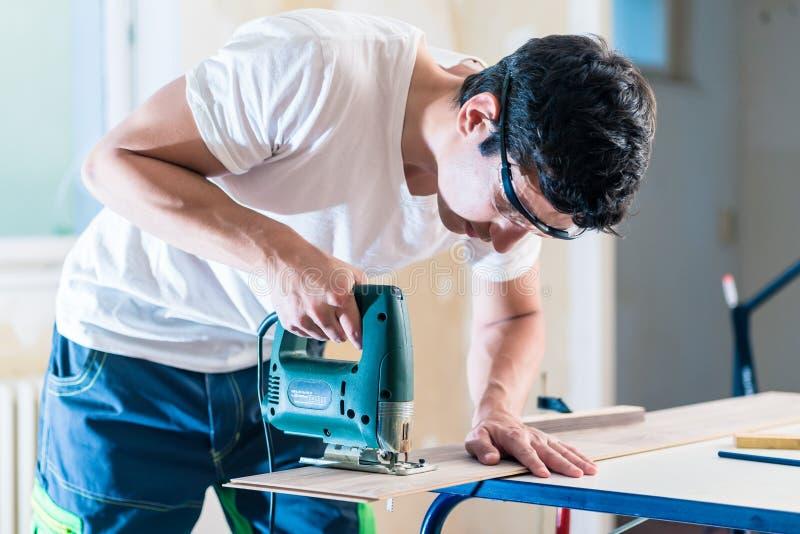 DIY-arbeider die houten paneel met kaliberzaag snijden royalty-vrije stock afbeelding