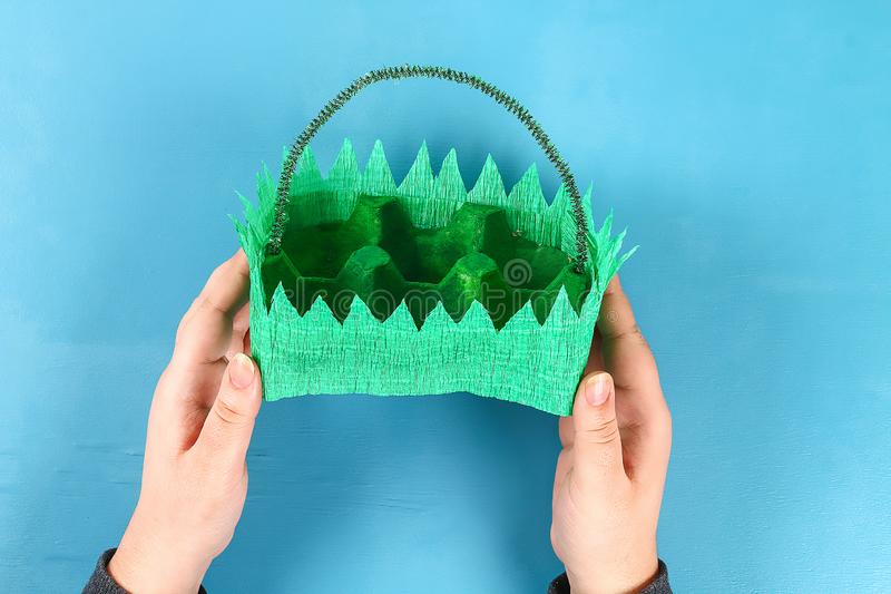 DIY basket Easter egg from cardboard tray, crepe paper, chenille stem on blue background stock photo