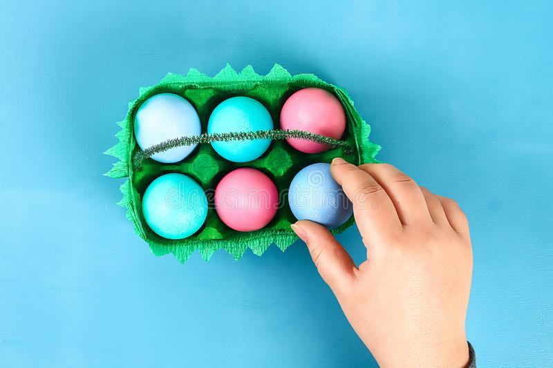 DIY basket Easter egg from cardboard tray, crepe paper, chenille stem on blue background stock image
