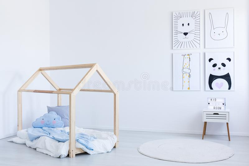 DIY bed in boy`s room. Blue bedsheets and pillows on wooden DIY bed in white boy`s room with contrast color drawings stock photography