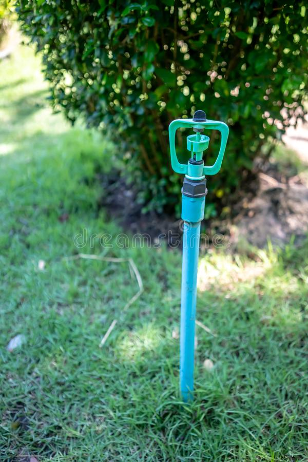 DIY blue garden sprinkler head with stand in the lawn garden stock images