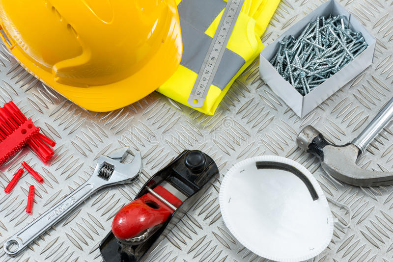 DIY or Carpentry Tools and Equipment on Steel Tread Plate. Carpentry DIY tools and safety gear including a hammer, face mask, hand plane, an adjustable wrench stock photo
