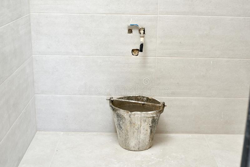 DIY, ceramic brick tile wall in a bathroom improvements room construction. Tap and filled bucket water. Reform renovation repair flat apartment indoor tools royalty free stock images