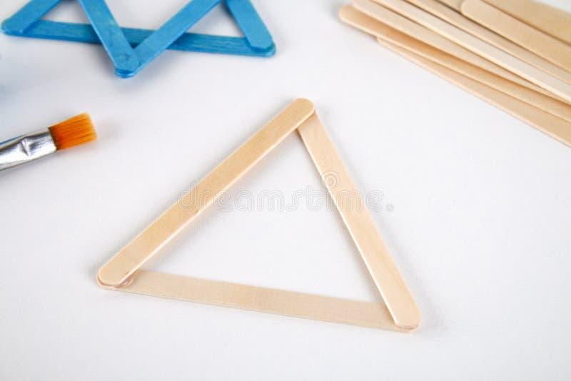 DIY Chanoekadecor Jodenster van roomijsstokken op een witte houten lijst Gids, stap voor stap op de foto Diy  stock foto's