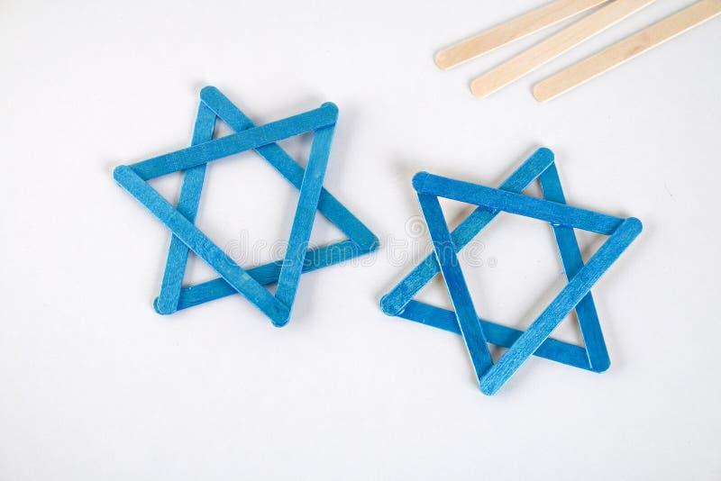 DIY Chanukkahdekor Davidsstjärna från glasspinnar på en vit trätabell Handbok stegvis på fotoet Diy på arkivbilder