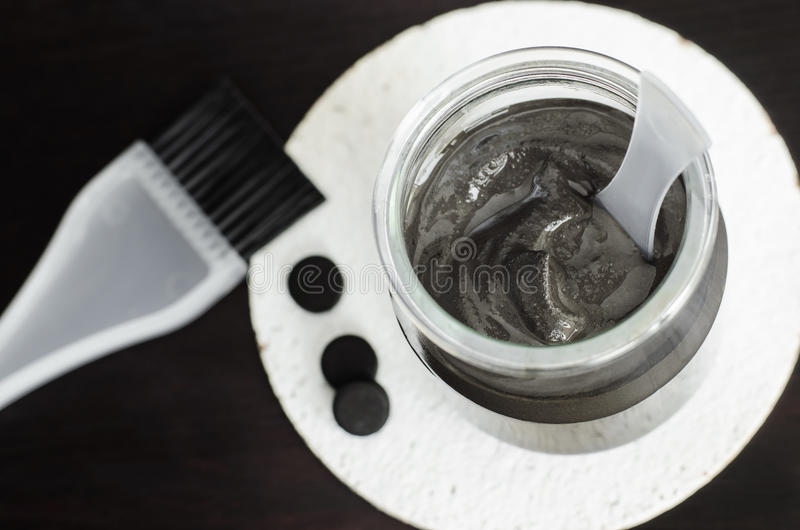 DIY charcoal face mask in a small glass jar. Homemade cosmetics. stock photos