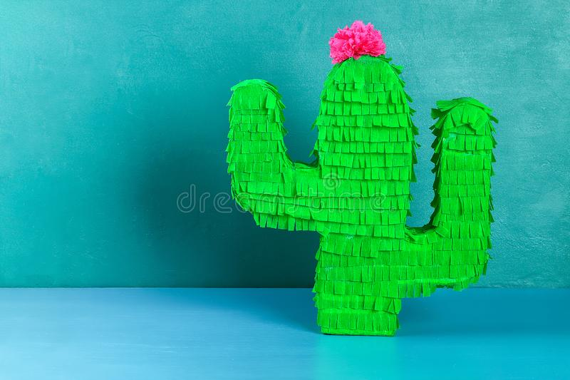 Diy cinco de mayo Mexican Pinata Cactus made cardboard, crepe paper your own hands blue background. Diy cinco de mayo Mexican Pinata Cactus made cardboard and royalty free stock images