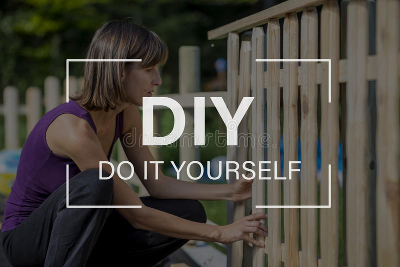 DIY concept with a woman building a garden fence. DIY - Do it yourself text with a woman building a garden fence placing an upright wooden slat in position to be stock photography