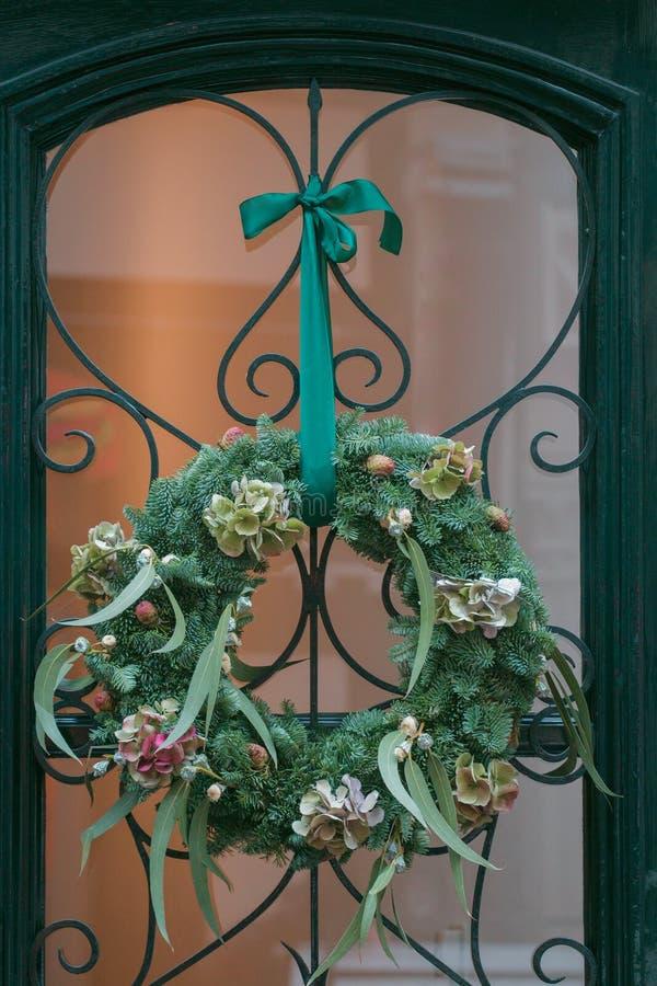 DIY conifer z eukaliptusa i hortensi wianku Bożenarodzeniowym kwiecistym obwieszeniem przy wejściowym drzwi obraz royalty free