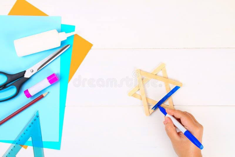 DIY Davidsstjärnan med hans händer från glass klibbar på en vit trätabell royaltyfria bilder