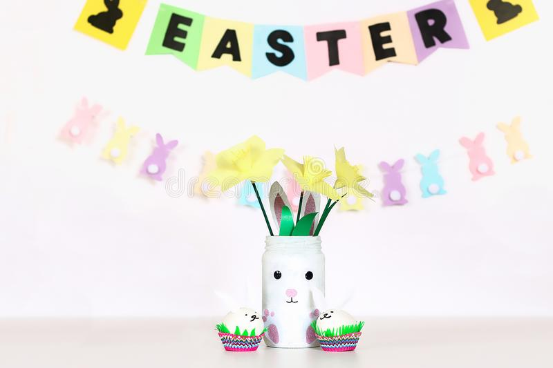Diy decor for Easter. Paper garlands, vase bunny, daffodils, eggs bunnies, basket with painted eggs royalty free stock photography