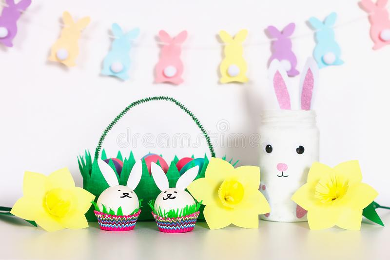 Diy decor for Easter. Paper garlands, vase bunny, daffodils, eggs bunnies, basket with painted eggs stock photos