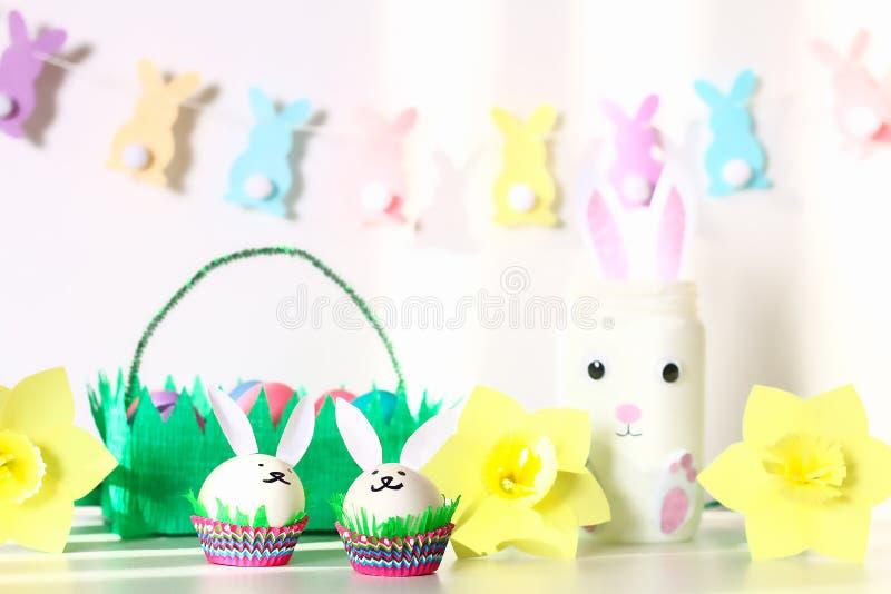 Diy dekor för påsk Pappers- girlander, vaskanin, påskliljor, äggkaniner, korg med målade ägg royaltyfria bilder