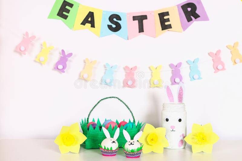 Diy-Dekor für Ostern Papiergirlanden, Vasenhäschen, Narzissen, Eihäschen, Korb mit gemalten Eiern lizenzfreies stockbild