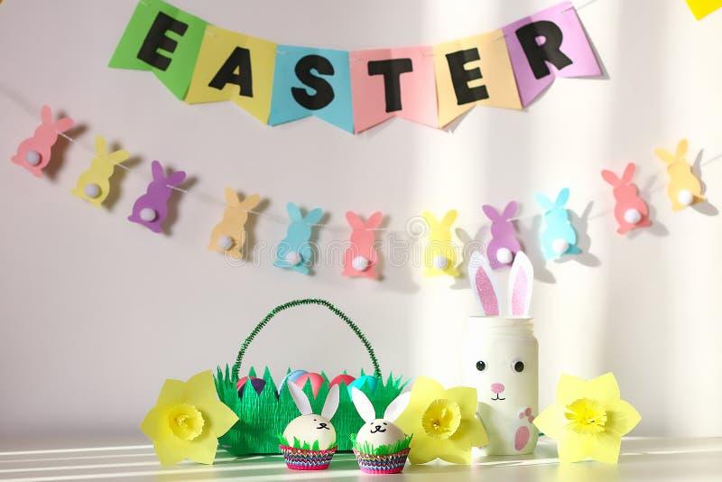 Diy-Dekor für Ostern Papiergirlanden, Vasenhäschen, Narzissen, Eihäschen, Korb mit gemalten Eiern stockbild