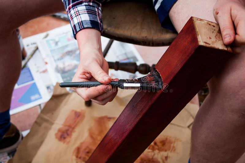 DIY or do it yourself concept with painting wood. Holding and painting wooden table leg. Painting brush in hand. Home improvements stock photography