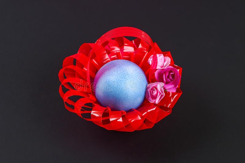 Diy Easter egg basket made of red plastic cup decorated with artificial flowers black background royalty free stock photography