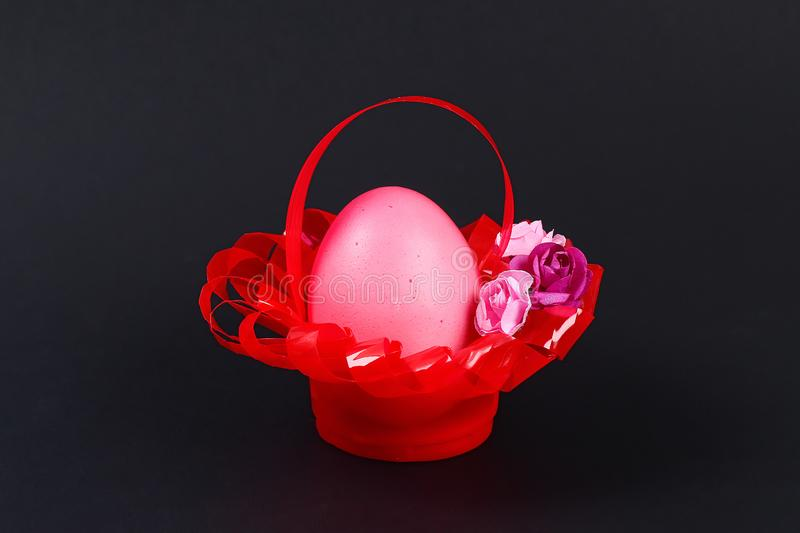 Diy Easter egg basket made of red plastic cup decorated with artificial flowers black background royalty free stock images