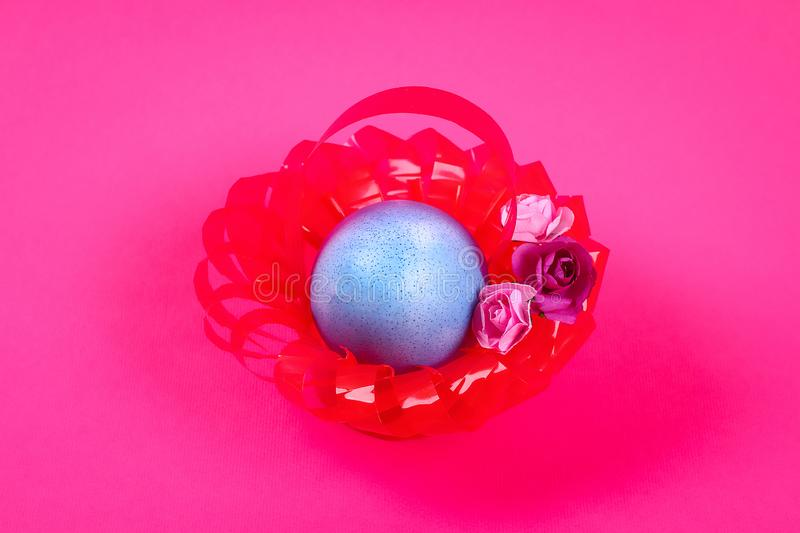 Diy Easter egg basket made of red plastic cup decorated with artificial flowers pink background stock photos