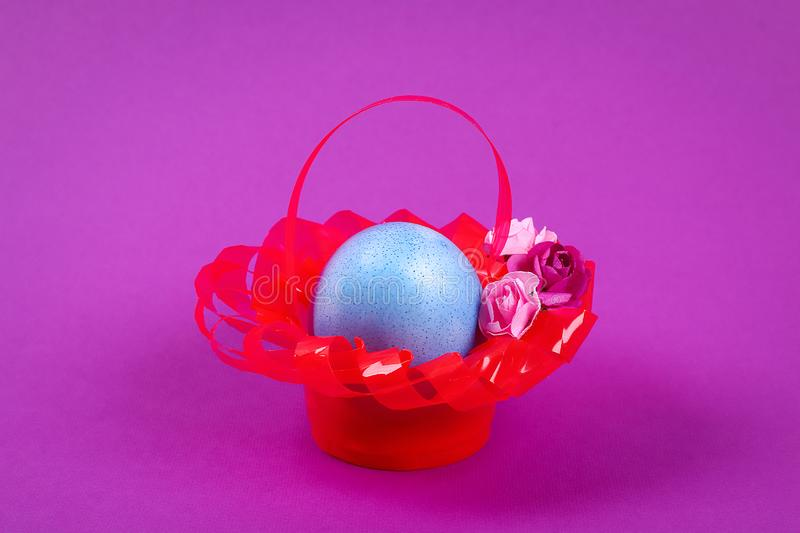 Diy Easter egg basket made of red plastic cup decorated with artificial flowers purple background royalty free stock images