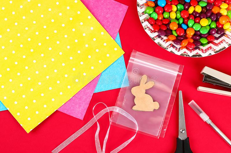 Diy Easter wrapping package sweets in a bag with a cut out bunny silhouette on a red background stock photography