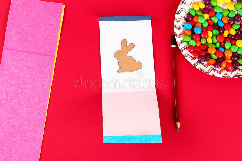 Diy Easter wrapping package sweets in a bag with a cut out bunny silhouette on a red background. Gift idea, decor Spring, Easter. Step by step. Top view stock photos