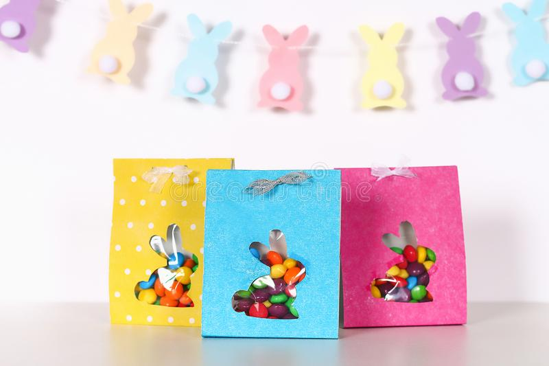 Diy Easter wrapping package sweets in a bag with a cut out bunny silhouette on a white background. Gift idea, decor Spring, Easter. Step by step. Process kid royalty free stock photography